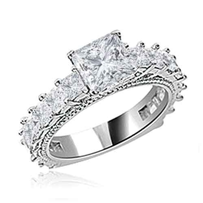 Diamond Essence Designer Ring With 1.50 Cts. of Princess in Center, Accompanied by Small Princess Stones Melee on band, 3 Cts.T.W. In Platinum Plated Sterling Silver.