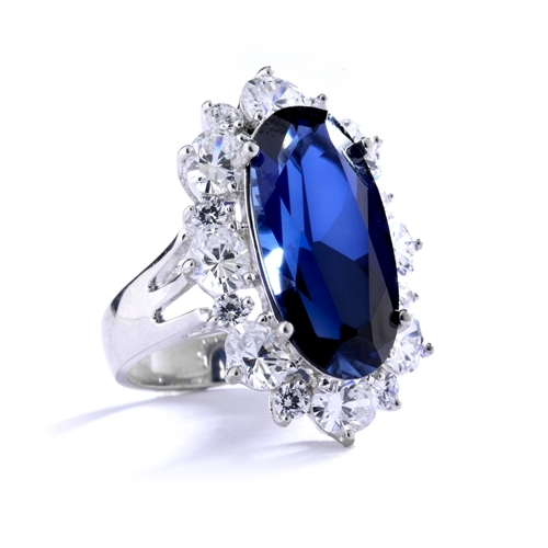 Sapphire Ring - 13 Cts. Long Oval cut Sapphire Essence set in center surrounded by Oval Diamond Essence and Melee. 16.0 Cts. T.W. set in Platinum Plated Sterling Silver.