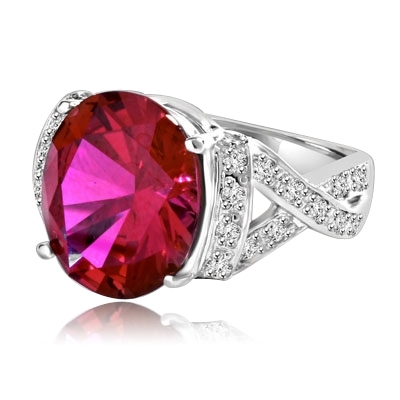 Ruby Ring- 6.0 Cts Oval Cut Ruby Essence in center accompanied by Melee on the band making criss cross design. 6.50 Cts. T.W. set in Platinum Plated Sterling Silver.