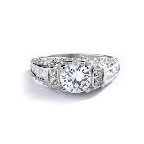 Engagement Ring- 1.0 Ct. round Brilliant Diamond Essence in center with Chanel set Baguettes and Melee going half way down the band. 2.0 Cts. T.W. set in Platinum Plated Sterling Silver.