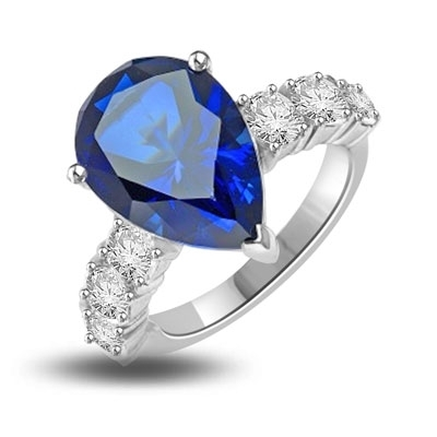 Diamond Essence Designer Ring with 5.50 cts. Pear Cut Sapphire Essence in center and three round stones on each side of center. 7.0 Cts. T.W. set in 14K Solid White Gold.