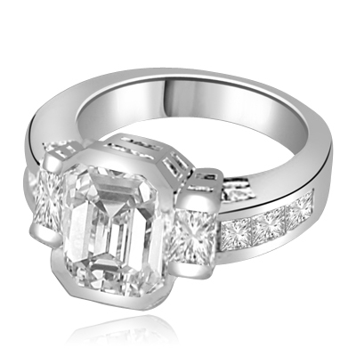 Not for the shy - this exquisite Ring with a 4 Ct. Bezel Set Radiant Emerald Cut Diamond Essence Masterpieces in the center and Princess Cut accents on both sides. 6 Cts. T.W, in 14K White Gold.