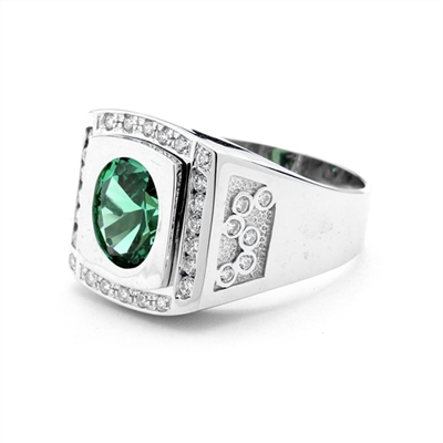 An impressive Men's Ring in two-toned 14K White Gold features a 4.0 cts. oval Emerald stone set flush in a platform of white gold surrounded by melee, with double jolts of melee on each shank. 4.50 cts. t.w.