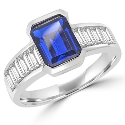 Escape with this Wide Band Ring with Channel Set Emerald Cut Sapphire Essence, 2.5 cts. separated by straight Diamond Bright Baguettes set vertically for a totally magnificent effect. 3.5 cts. T.W. set in 14K Solid White Gold.