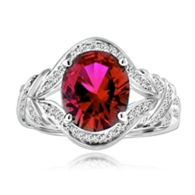 All eyes oval-cut 4.0 cts. Diamond Essence ruby at the center of this 14k Solid White Gold ladies ring, encircled by Diamond Essence melee that culminates in a fancy knotted shank. Spicy! 4.10 cts. t.w.