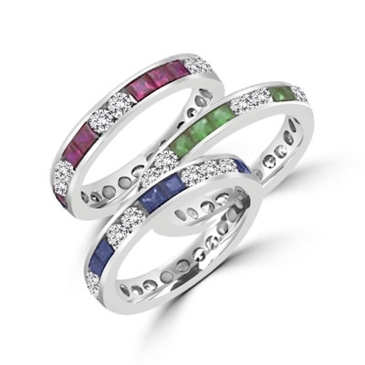 Best selling Eternity Bands with Princess Cut simulated Emeralds and Round Cut Diamond Essence stones all around the band. 1.5 Cts. T.W, in 14K White Gold.
