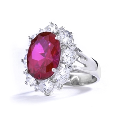 Gorgeous Ring with 8.25 Cts. Oval Cut Ruby Essence in center, surrounded by Oval cut Diamond Essence and Round Brilliant Melee. 10.25 Cts T.W. set in 14K Solid White Gold.