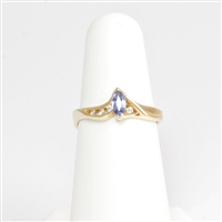 Lovely violet-hued marquise shaped tanzanite accented with channel set round brilliant cut diamonds in swirly 14K yellow gold ring.
