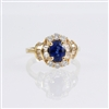 Oval blue sapphire with accents of round and baguette diamonds in 14K yellow gold.