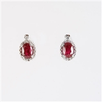 Oval shape Ruby and diamond earrings in 14K white gold.
