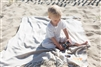 Adorable baby playing on the beach and laying on his personalized Blanket in Sand color with NEON personalization.