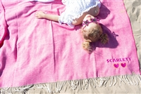 Wild pink blanket laying on the beach personalized with neon orange thread colors and heart sunglasses as the graphic.