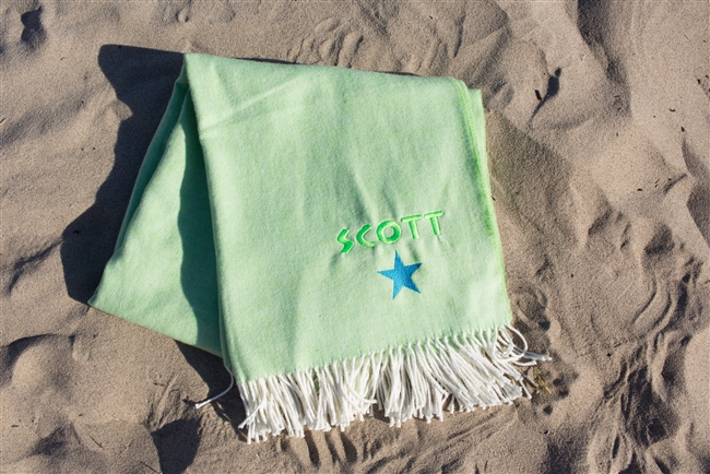 Lime Blanket laying on the beach personalized with neon green thread colors and a neon blue star graphic.