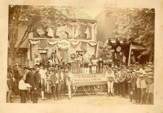 Photograph of Group of Men in Costume, Surrounding the Parade Wagon of E. A. Bloser Wholesale & Retail Jeweler. Elias Alexander Bloser.Newville, PA.[1890]