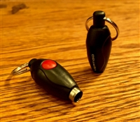 small, football shaped, black punch cutter with a red button