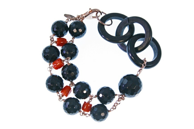 "Round faceted Black Onyx Gemstones are accented by Red Coral Nuggets. A single large Onyx bead and three links of natural Black Horn create an asymmetrical look. 925 Rose Gold plated Sterling Silver Chain & Lobster Clasp. 7 1/2"" in Length adjustable to 7"""