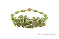 Uniquely handcrafted in the US by Silver Pansy, this Bracelet features lustrous White Keshi Pearls filled with Peridot Gemstones and reminds one of a bouquet of flowers. The band is finished with additional Gemstones on Gold Filled wire clasp.