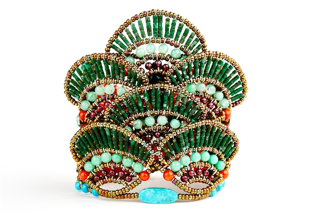 A beautiful & unique Statement Cuff Bracelet, Naga is sure to garner you many compliments. This dimensional piece reminds one of a peacock. Done in Green Serpentine, Turquoise & Coral. Hand crafted in Italy by Ziio. Button Closure, adjustable in length.