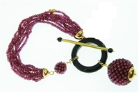 Garnet Gemstone Bracelet filled with Italian style - eight strands of Purple Garnets are accented with a ring of hand cut Black Onyx. The ring is accented with two spheres hand woven with small Garnet Beads, one as a charm drop from the ring. 18k gold