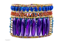 A stunning Designer Cuff Bracelet by Ziio features large polished Amethyst Gemstones, accented with Blue Lapis & Rust Red Carnelian Gemstones. White Pearls & Murano Glass Beads frame & define. 925 Sterling Silver Button Closure, adjustable length. Large