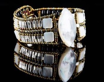 Ziio's Marquise Cuff Bracelet with a large White, opalescent Mother of Pearl  at the center surrounded by additional Pearl beads, Sterling Silver Beads. Black Onyx Gemstones add contrast at the back. Made in Italy on stainless steel wire