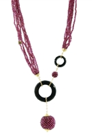 long necklace with eight strands of Purple Garnets are accented with two rings of hand cut Black Onyx. Asymmetrical in design, the rings are accented with two spheres hand woven with small Garnet Beads, one as a drop from the larger ring.  18k Yellow Gold