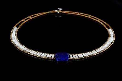 "Ziio's Armonia Necklace in Lapis & Pearl. One large faceted Lapis Gemstone is at the center  with a contrast band of White Seed Pearls framed in Murano Glass Beads. Sterling Silver Button Closure. Length is 18"", adjustable to 15""."