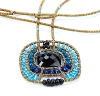 From Ziio's Twilight Collection. This striking Pendant Necklace has a Black Onyx Gemstone at the center, surround by multi-shades of Blue & Black Gemstones. Turquoise, Lapis, Zircon, Tourmaline, Brass & Murano Glass Beads. Hand crafted in Italy.