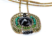 From Ziio's Twilight Collection. This striking Pendant Necklace has a Black Onyx Gemstone at the center, surround by multi-shades of Green & Black Gemstones. Jade, Malachite, Tourmaline, Brass & Murano Glass Beads. Hand crafted in Italy.