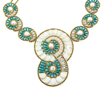 "A stunning statement Bib Necklace by Ziio.  Aptly named ""Shell"", the design is reminiscent of a beautiful Conk Shell and it's swirling design. Beaded with Turquoise beads, white Water Pearls and Mother of Pearl. Hand crafted in Italy on stainless steel"