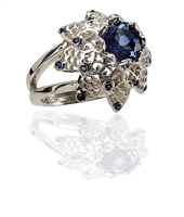From Brenda Smith's Lace Collection, this ring is done in non-tarnishing White Sterling Silver with lab created Blue Sapphires. The center gemstone is 7mm, 1.64ctw with an additional 0.64ctw Sapphires as accents. Size 7. Can be re-sized.