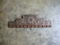Available in twenty four inches only. This is a stair step design with a punched floral concho in the center. Running below and evenly spaced are metal clavos with rounded smooth heads.