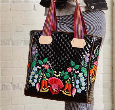 Ladies Tote bag in shiny black with floral embroidery with striped web handles and leather trim.