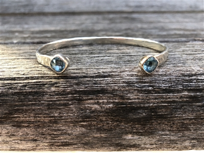 Sterling silver hammered bangle bracelet with blue topaz