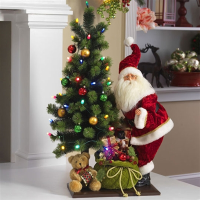 "RAZ IMPORTS 34"" SANTA TRIMMING A LIGHTED TREE"