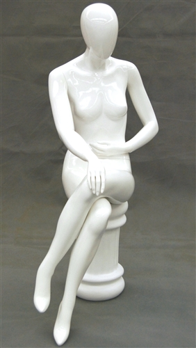 Female egghead mannequin in seated pose.  Her legs are crossed with her hands on her lap.