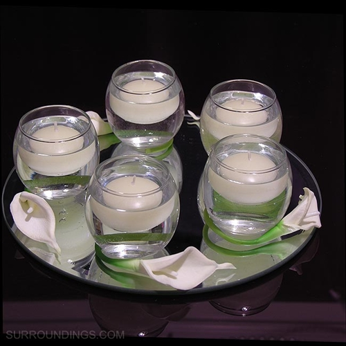 "Mini calla lily flowers wrap around votive cups on a 10"" beveled mirror"