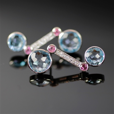 Imperial Icicle Earrings photo. Like the Imperial Icicle Ring, these are made from 18k white gold, giving it a special unique appeal. Two, round, shiny, blue topaz stones at each end and 2 smaller pink tourmalines along with the diamonds on the shaft.