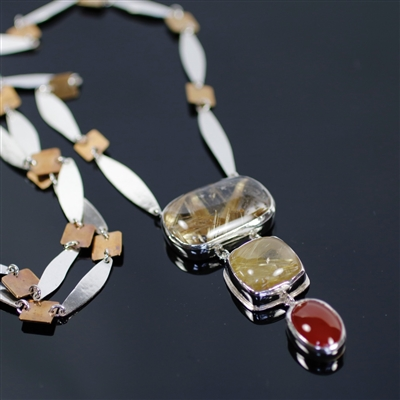 Burning Embers Necklace photo. Silver structure, the string has silver thins in long almond shapes with squares of bronze in between and the pendant has three stones: rectangular and squared rutilated quartz and an oval cornelian. Fiery complection!