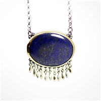 Bright blue lapis is set in bezel of 18k gold back with sterling silver.