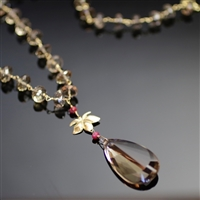 Aurora's Charm Necklace photo. Gorgeous smoked quartz stones make up most of the necklace. They are combine by 18k yellow gold hooks and have a gold lotus flower that attaches the top part to the big, drop shaped smoked quartz stone and little red rubies.