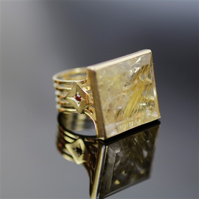 Majestic Tabletop Ring photo. beautifully structured 18k yellow gold shines with royalty with the strong, squared shaped rutilated quartz and the red garnet on the side details the sophisticated tabletop perfectly.