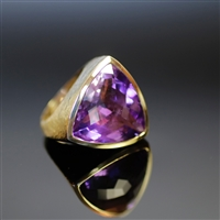 Cosmic Violet Ring photo. This flawless beauty engages the eye like no other, its feel is amazing as well. The round triangular shape of the shiny, purple Amethyst is a super power. the 18K gold helps bring in the focus to the piece. Details inside.