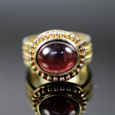 Sultry Sovereign Ring photo. This is a very royal design, The 18k yellow gold really combines well with the round, center red rhodolite creating a Sultry Sovereign. The details are little dots and braided designs on the sides.