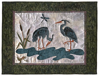 Quilt block of two herons near a stream being watched by a frog and a dragonfly.