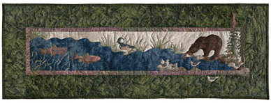 Quilt block of a brown bear fishing in a river.