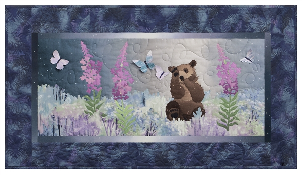 Quilt block of a brown bear cub playing with butterflies in a field of wildflowers.