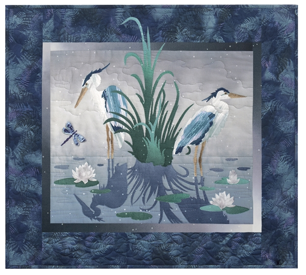 Quilt block of two blue herons standing in a pond, surrounded by lily pads and a dragonfly.