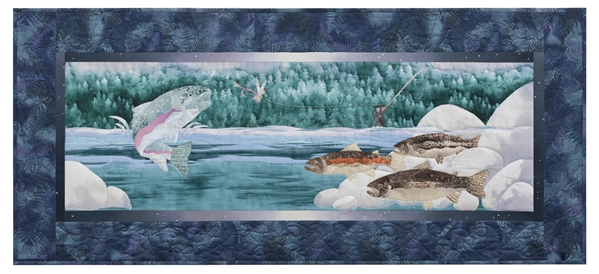 Quilt block of a fisherman catching a rainbow trout that is jumping out of the water, while other trout swim near the river rocks