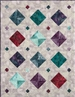 Pieced quilt pattern of simple diamonds made out of sparkly fabric
